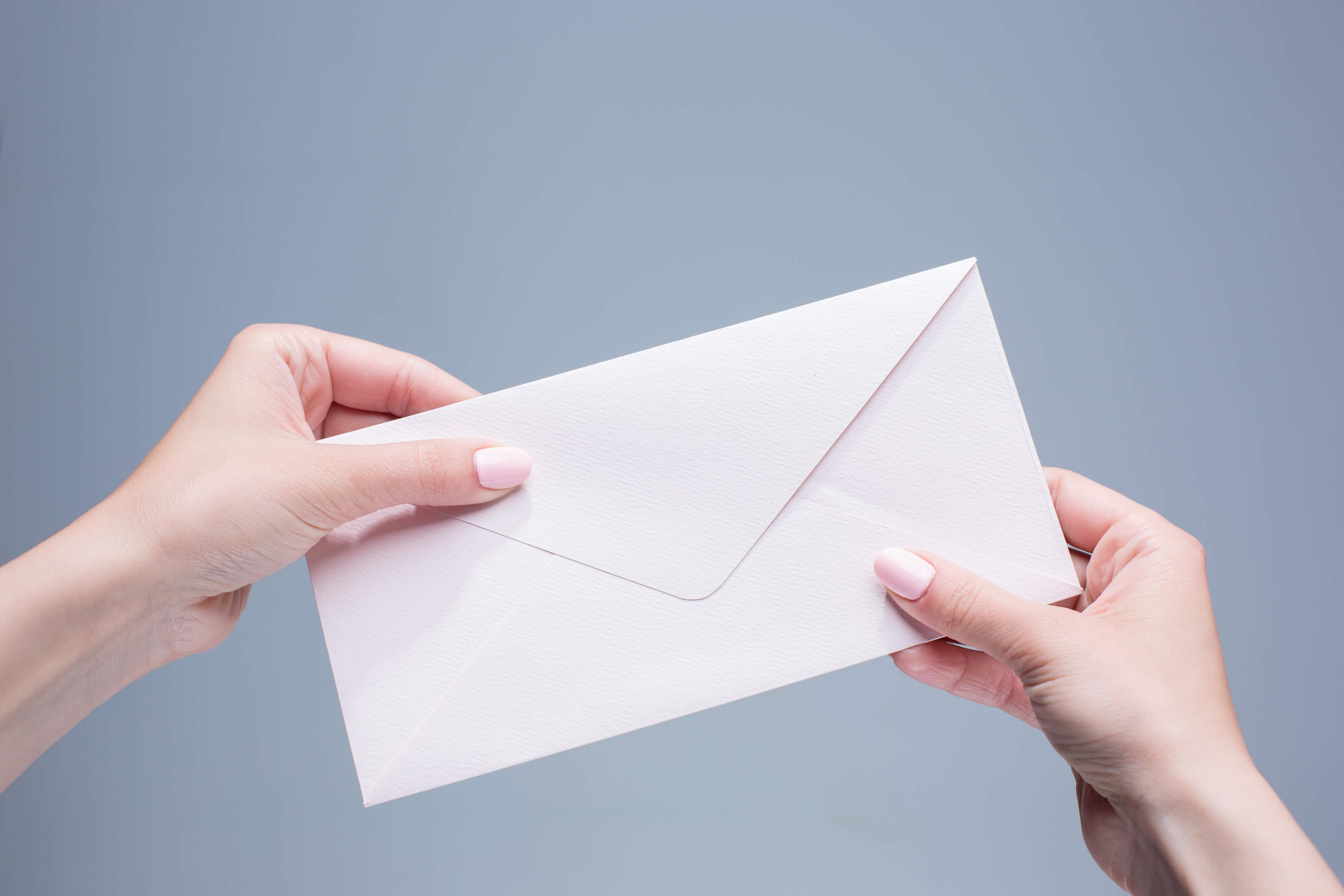 Female Hands With The Envelope Against The Gray Background 1